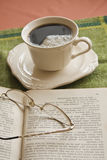 Cup of coffee, book in background royalty free stock photos