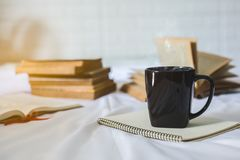 Cup of coffee and a book on a bed royalty free stock image