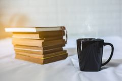 Cup of coffee and a book on a bed royalty free stock photos