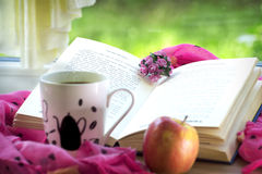 A cup of coffee and a book. A cup of coffe, an apple and a romantic book Royalty Free Stock Photos
