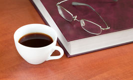 Cup of coffee with book and glasses Stock Photo