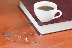 Cup of coffee with book and glasses Stock Photography