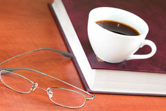 Cup of coffee with book and glasses Stock Photos