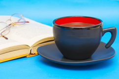 Cup of coffee with book isolated on blue background Royalty Free Stock Photos