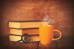 Cup of coffee and book with loupe Stock Image