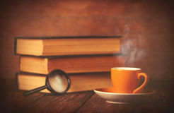 Cup of coffee and book with loupe Royalty Free Stock Photo