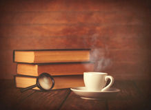 Cup of coffee and book with loupe Stock Photo