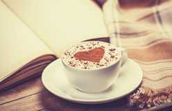 Cup of coffee and book with scarf. Photo in old color image style Stock Image