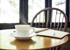 Cup of coffee with book on table in cafe. Cup of coffee with book on table in shop cafe interior Royalty Free Stock Photo