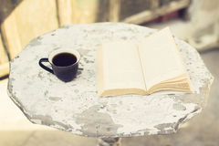 Cup of coffee and book on a table outdoors Royalty Free Stock Photo
