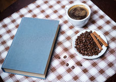 Cup of coffee and book on the tablecloth. Cup of coffee with beans and book on the tablecloth Royalty Free Stock Photography