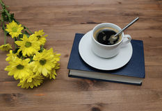 Cup of coffee and book with yellow flowers onwooden table Royalty Free Stock Images