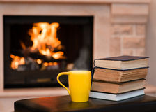 Cup of coffee with books on the background of the fireplace Royalty Free Stock Photo