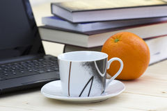 Cup of coffee, books, laptop and orange Stock Photo