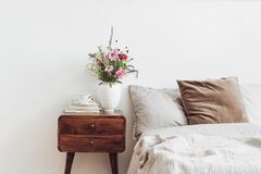 Cup of coffee and books on retro wooden bedside table. Rustic white ceramic vase with bouquet of pink cocmos and zinnia
