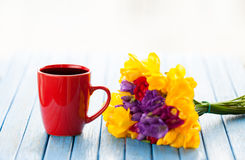 Cup of coffee and bouquet of flowers Stock Images