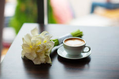 Cup of coffee and bouquet flowers on table in cafe Royalty Free Stock Image
