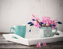 A cup of coffee and  bouquet of flowers on a wooden table Stock Images