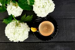 Cup of coffee with bouquet hydrangea. Cup of coffee with bouquet flower hydrangea on black wooden background. Good morning. Flat lay. Top view Stock Photos