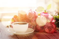 Cup of coffee and bouquet pink roses on table Stock Photo