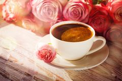 Cup of coffee and bouquet pink roses on table Stock Photos