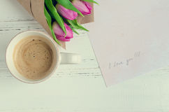 Cup of coffee with bouquet of pink tulips and notes I LOVE YOU Royalty Free Stock Images