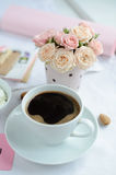 Cup of coffee and a bouquet of roses Stock Photos