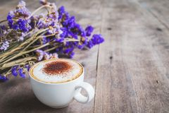A cup of coffee with bouquet of violet dried flowers on wooden f Royalty Free Stock Photo