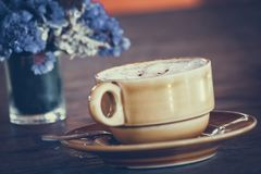 A cup of coffee and a bouquet on wooden teble stock images