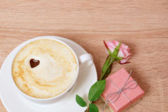 A cup of coffee, a box with a gift and one rose. Wooden table Stock Image