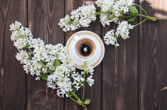 A Cup of coffee and a branch of lilacs on a wooden table. A Cup of a Cup of coffee and a branch of lilacs on a wooden tablecoffee and a branch of lilacs on a Royalty Free Stock Photography