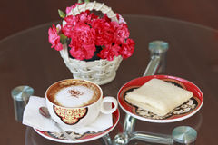 A cup of coffee and bread and flower. On table royalty free stock photography