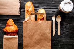 Cup coffee and bread in paper bag on wooden background Stock Photography