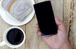 A cup of coffee, bread on white plate, smartphone in hand on woo Stock Image