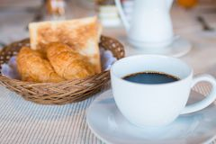 Cup of coffee. Breakfast with coffee and croissants in a basket on table.  Royalty Free Stock Images