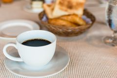 Cup of coffee. Breakfast with coffee and croissants in a basket on table.  Royalty Free Stock Photo