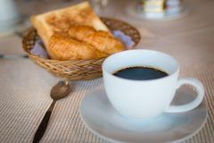 Cup of coffee. Breakfast with coffee and croissants in a basket on table.  Stock Images