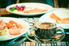 Cup of coffee with breakfast food on the table Instagram vintage. Style Stock Photography
