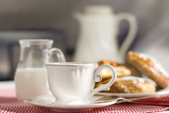 Cup of coffee with a brioche Stock Images