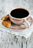 Cup of coffee and broken cookie Stock Photos
