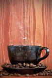 Cup of  coffee on a brown background with coffee beans Royalty Free Stock Photo
