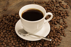 Cup of coffee and brown beans around. Royalty Free Stock Photography