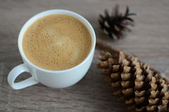Cup of coffee and brown pine cone Royalty Free Stock Image