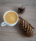 Cup of coffee and brown pine cone Royalty Free Stock Photography