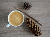 Cup of coffee and brown pine cones Stock Images