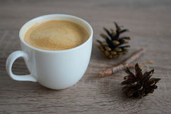 Cup of coffee and brown pine cones Royalty Free Stock Photos
