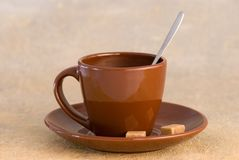 Cup of coffee with brown sugar. Side view of cup of coffee on saucer with spoon and brown sugar lumps Stock Image