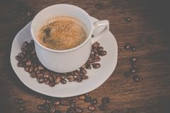 A Cup of Coffee on Brown Wooden Table With Coffee Seeds Royalty Free Stock Image