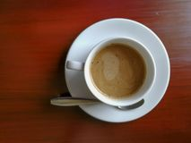 Cup of coffee on brown wooden table, top view. Cup of coffee on brown wooden table, top view Stock Photography