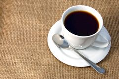 Cup of coffee on burlap. A shot of a cup of coffee on burlap Royalty Free Stock Photos